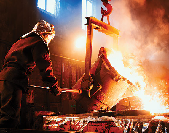 Foundry worker pouring metal