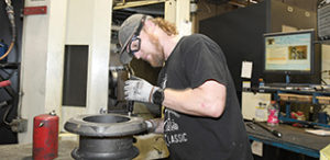 Manufacturing worker checking metal part