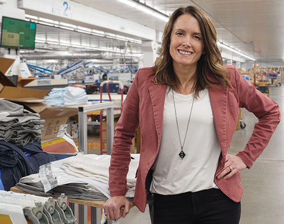 Lakeshirts Michelle Daggett poses in front of production area - Enterprise Minnesota magazine
